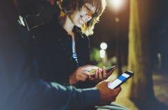 Les gens dirigeant ensemble le doigt sur le smartphone d'écran sur la lumière de bokeh de fond dans la ville atmosphérique de nui photographie stock libre de droits