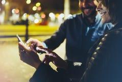 Les gens dirigeant ensemble le doigt sur le smartphone d'écran sur la lumière de bokeh de fond dans la ville atmosphérique de nui images libres de droits