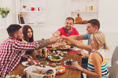 Les gens disent des verres de tintement d'acclamations au dîner de fête de table Images libres de droits