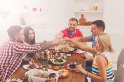 Les gens disent des verres de tintement d'acclamations au dîner de fête de table Photo stock