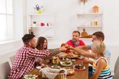 Les gens disent des verres de tintement d'acclamations au dîner de fête de table Photographie stock