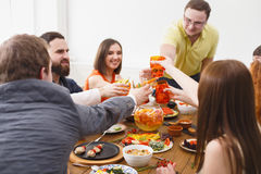 Les gens disent des verres de tintement d'acclamations au dîner de fête de table Photographie stock libre de droits
