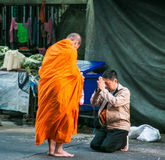 Les gens donnant l'aumône au bouddhiste images libres de droits