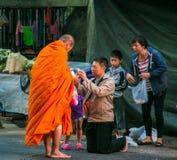 Les gens donnant l'aumône au moine bouddhiste images stock
