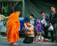 Les gens donnant l'aumône aux moines bouddhistes image stock