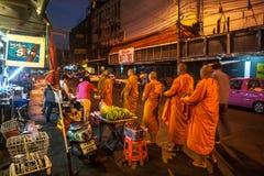 Les gens donnant l'aumône aux moines bouddhistes images stock