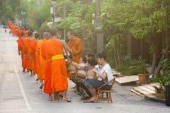 Les gens donnant l'aumône aux moines bouddhistes sur la rue, Laos image stock