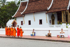 Les gens donnant l'aumône aux moines bouddhistes sur la rue, Laos photos stock