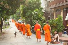 Les gens donnant l'aumône aux moines bouddhistes sur la rue, Laos photographie stock libre de droits