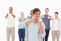 Les gens donnant les pouces- avec une femme souriant dans le premier plan Photo libre de droits