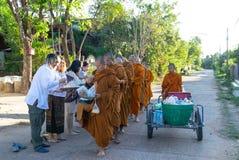 Les gens donnent l'aumône à un moine bouddhiste, à des croyances et à une culture religieuse photographie stock libre de droits