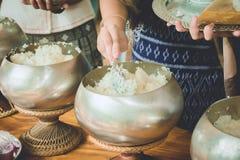 Les gens donnent le riz dans la cuvette d'aumône de moine bouddhiste, nourriture offrant les FO images libres de droits