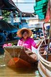 Les gens du pays thaïlandais vendent la nourriture et les souvenirs au marché de flottement célèbre de Damnoen Saduak, Thaïlande Photographie stock libre de droits
