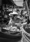 Les gens du pays thaïlandais vendent la nourriture et les souvenirs au marché de flottement célèbre de Damnoen Saduak, Thaïlande Image libre de droits