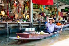 Les gens du pays thaïlandais vendent la nourriture et les souvenirs au marché de flottement célèbre de Damnoen Saduak, Thaïlande Photographie stock