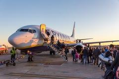 Les gens embarquant sur Ryanair voyagent en jet l'avion commercial sur l'aéroport de Valence au coucher du soleil Image libre de droits