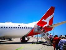 Les gens embarquant un type d'avions domestique de ligne aérienne de Qantas : Boeing 737 sur la piste image libre de droits