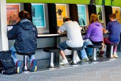 Les gens employant une station de charge d'ordinateur portable à un aéroport Images libres de droits