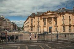 Les gens en bâtiment néoclassique avant, pavé rond et ciel nuageux à Paris photo stock