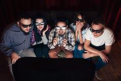 Les gens en verres 3d regardent la TV, stupéfaite par des effets Photographie stock libre de droits