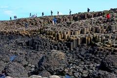 Les gens escaladant la chaussée de Giants et les falaises, Irlande du Nord Photo stock