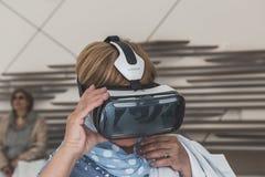 Les gens essayant le casque 3D à l'expo 2015 à Milan, Italie Image stock
