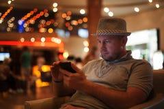 Les gens et le concept de technologie - homme heureux avec le message de lecture de smartphone à la barre ou au bar Image stock