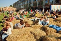 Les gens et les jeunes familles détendant dans le foin en raison du festival extérieur de ville Photographie stock