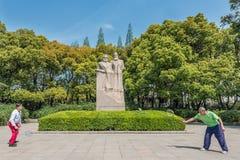 Les gens exerçant le badminton marx et la statue d'Engels à fuxing par Photos libres de droits