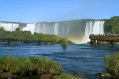 Les gens explorant le site de patrimoine mondial puissant de l'UNESCO des chutes d'Iguaçu avec un arc-en-ciel magnifique photo libre de droits