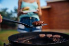 Les gens faisant cuire le rassemblement sur le gril de barbecue dehors Photo libre de droits