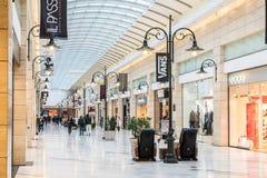 Les gens faisant des emplettes dans l'intérieur de luxe de centre commercial Photos stock