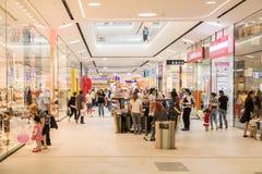 Les gens faisant des emplettes dans l'intérieur de luxe de centre commercial Image libre de droits