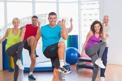 Les gens faisant la forme physique de puissance s'exercent à la classe de yoga Images libres de droits
