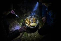 Les gens faisant un gril avec de la viande et des fruits la nuit en Allemagne Photographie stock