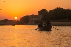 Les gens faisant un tour de bateau sur le lac gadi Sagar dans Jaisalmer au coucher du soleil avec le soleil ? l'arri?re-plan images libres de droits