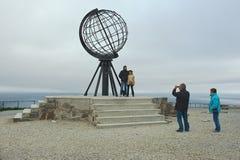 Les gens font la photo de voyage avec le globe symbolique au cap du nord, Norvège Photo libre de droits