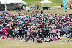 Les gens font la pose du guerrier II dans la classe extérieure massive de yoga photos stock