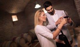 Les gens goûtant le vin en sous-sol d'établissement vinicole photo stock