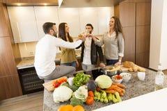 Les gens grillant avec du vin blanc dans la cuisine Photographie stock
