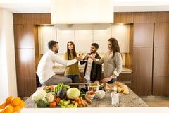 Les gens grillant avec du vin blanc dans la cuisine Image stock