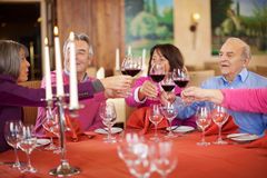 Les gens grillant des verres de vin au restaurant Images libres de droits