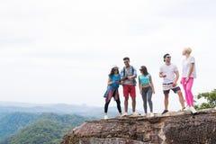 Les gens groupent avec des sacs à dos se tenant sur le dessus de montagne apprécient parler, jeunes hommes et femme de paysage Photographie stock libre de droits