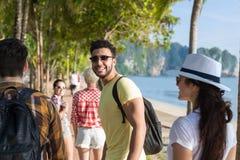 Les gens groupent la marche en parc de palmier sur la plage parlant, touristes occasionnels d'amis Photographie stock libre de droits