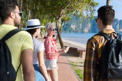 Les gens groupent la marche en parc de palmier sur la plage parlant, touristes occasionnels d'amis Photographie stock