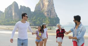 Les gens groupent la marche sur la plage au-dessus des montagnes parlant les jeunes hommes et les touristes de sourire heureux de banque de vidéos