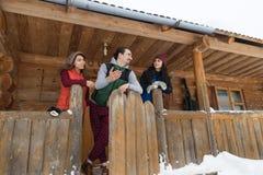 Les gens groupent le cottage en bois de station de sports d'hiver de neige d'hiver de maison de campagne Image libre de droits