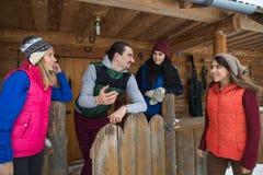 Les gens groupent le cottage en bois de station de sports d'hiver de neige d'hiver de maison de campagne Photographie stock libre de droits