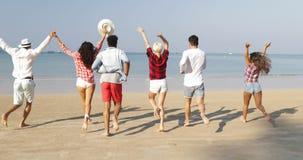 Les gens groupent le fonctionnement pour arroser sur les hommes gais heureux et les femmes de vue arrière de dos de plage élevant clips vidéos