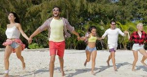 Les gens groupent le fonctionnement sur la plage tenant des mains, hommes de course de mélange et les femmes heureuses apprécient banque de vidéos